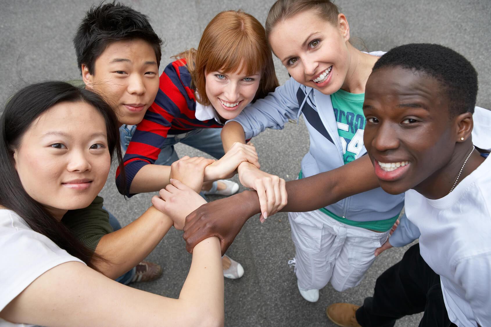 Gruppe von jungen Menschen, jeder Kultur und Herkunft, die einander die Hand geben und in die Kamera lächeln.